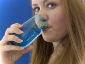 stock photo of chug  - Woman drinking water out of a colored glass - JPG
