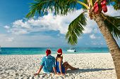 Couple in blue clothes on a tropical beach at christmas