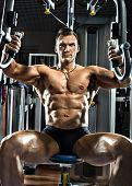 stock photo of execution  - very brawny guy bodybuilder execute exercise on gym apparatus Butterfly Machine in gym - JPG