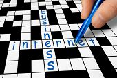 Hand filling in crossword - Business and Internet