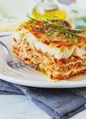 stock photo of lasagna  - serving freshly cooked lasagna on a dining table close up - JPG