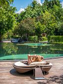 Young woman relaxing at the pool at tropical resort in Thailand