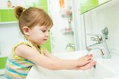 Cute little girl washing her hands in bathroom