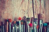 stock photo of messy  - row of artist paintbrushes closeup on old wooden rustic table retro stylized - JPG