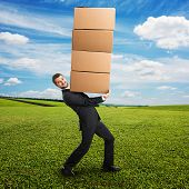 smiley young businessman looking at camera and carrying four heavy boxes on the hands. photo at outdoor