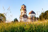 Wild Flowers In The Evening Light On The Background Of An Abandoned Church In Novgorod Region, Russi