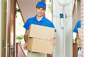 Smiling male postal delivery courier man indoors delivering parcel package boxes
