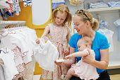 woman choosing children apparel with little baby child and girl on hands in clothing shop supermarket