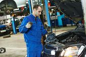 Auto mechanic checking oil level in car engine at garage service station