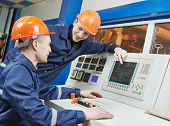 two operative industrial engineer workers discussing manufacture process near control panel system