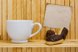 image of pastarelle  - Small eclairs on a shelf next to the cup - JPG