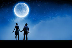 stock photo of enamored  - Silhouettes of young romantic couple standing under the moon light - JPG