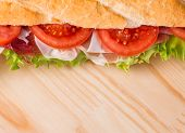 pic of baguette  - Ham and cheese salad submarine sandwich from fresh baguette on wooden background - JPG