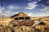 stock photo of wrecking  - Historic car wreck with bullet holes stands in the abandoned back country - JPG