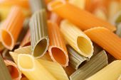 image of noodles  - Closeup of colorful raw Penne Rigate noodles pasta - JPG