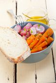 pic of root vegetables  - bowl of steamed root vegetable on a rustic white wood table - JPG