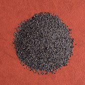 image of opiate  - Top view of poppy seeds against red vinyl background - JPG