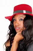 image of woman red blouse  - A closeup of a African American woman in a black blouse and long black  curly hair with a red hat isolated for white background - JPG