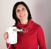 stock photo of cake-mixer  - Portrait of a smiling woman holding an electric mixer - JPG