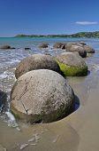 stock photo of maori  - Moeraki Boulders are perfectly sperical rocks on the beach at Moeraki near Oamaru - JPG