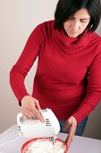 foto of cake-mixer  - Studio shot of a woman with an electric mixer - JPG