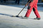 stock photo of paving  - Construction worker in safety shoes cleaning building site after paving work - JPG