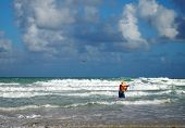 stock photo of breaker  - A man in a straw hat casts his fishing line out into the surf while standing in the breakers on the beach - JPG