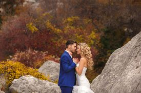 stock photo of tied hair  - Groom - a young dark-haired man in a blue suit and pink wedding tie - butterfly and blue-eyed bride - curly blond with long hair and a white wedding dress, posing, hugging in the park. ** Note: Visible grain at 100%, best at smaller sizes - JPG