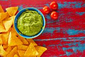 image of nachos  - Mexican food nachos and guacamole in red grunge background - JPG
