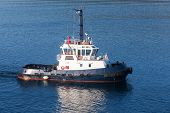 picture of dark side  - Tug boat with white superstructure and dark blue hull underway side view - JPG