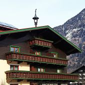 pic of chalet  - Tradition wooden alpine mountain chalet with carved balcony on winter ski resort in Alps - JPG