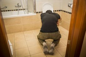 stock photo of vomiting  - Rear View of a Drunk Young Man Vomiting in the Toilet at Home While in Kneeling Position - JPG