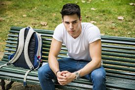 picture of sitting a bench  - Young Male Student Sitting on the Bench in a Park - JPG