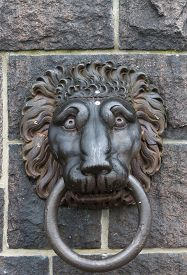 image of metal sculpture  - sculpture made from metal lion head with ring in mouth - JPG