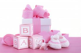 picture of teething baby  - Baby shower Its a Girl pink gift with baby booties dummy and gift box on pink shabby chic wood table - JPG