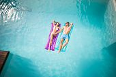 High angle view of happy couple relaxing on inflatable raft at swimming pool poster