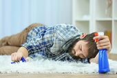 Funny young man tired of cleaning carpet at home poster