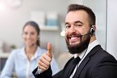Picture showing happy man in call center poster