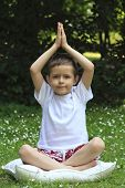 6 years old boy meditating outdoor