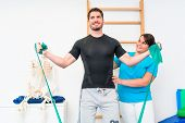 Young man exercising with resistance band in physical therapy poster