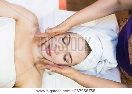 poster of Beautiful Girl Enjoys Face Massage In Spa Salon. Procedures For Beauty And Rejuvenation. Thai Massag