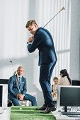 Young Multiethnic Businessmen In Formal Wear Playing Golf In Office poster