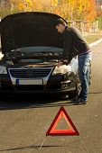 A Young Man Is Standing By A Broken Car And Looks Under The Car Hood.a Young Man, A Broken  Car And  poster