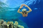 Beautiful woman free dives to explore a Coral reef in the Sea