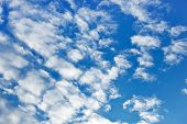 Fleecy clouds on blue sky background