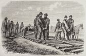 Antique illustration of  workers setting rails of the Union Pacific Railroad. Original, from drawing