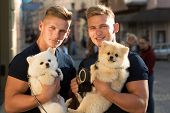 Carefree Time Together. Twins Men Hold Pedigree Dogs. Muscular Men With Dog Pets. Happy Twins With M poster