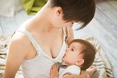 Mother Breastfeeding Baby In Her Arms At Home. Mom Breast Feeding Her Newborn Child. Baby Eating Mot poster