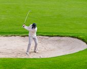 male golfer about to hit out of a sand bunker