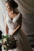 Gorgeous Beautiful Bride With Bouquet Posing At Window In Soft Light. Happy  Bride In Stylish Gown A poster